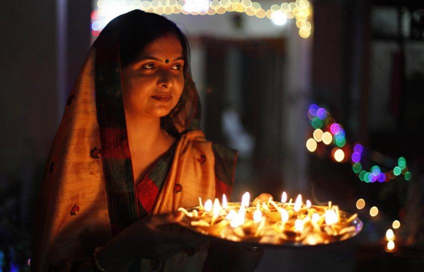 women with diwali lamps